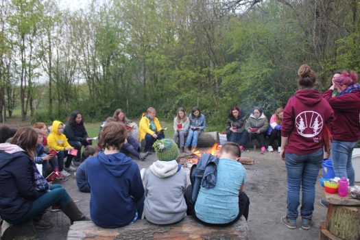 children and adults sitting around a campfire