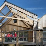 Photo of wooden school building with group of children in red jumpers standing outside on the wooden decking