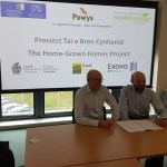"Two men sitting at a table signing a contract with powerpoint display behind with project title ""Home Grown Homes"""