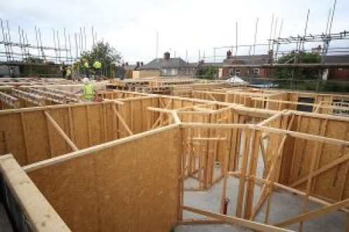 Building site showing timber frame structure being erected