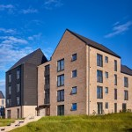 Multistory housing block with black timber cladding set against blue sky and green grass