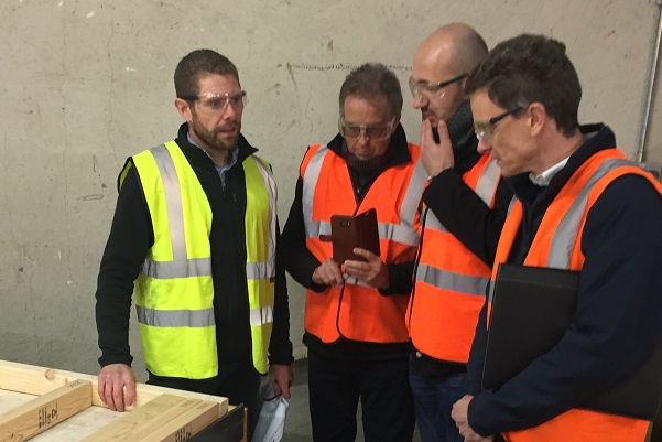 Group of men in high visibility jackets standing around looking at mobile phone in a timber house manufacturing factory