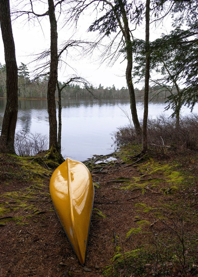 Yellow canoe is upside down on the shore. Frozen Lake is in the background.