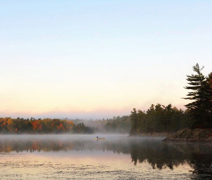Woman canoes on a misty morning at La Peche Lake