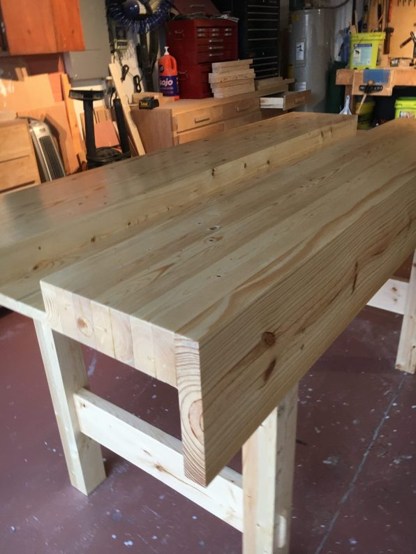 My new Workbench made from 2x4 and 2x6 stud grade lumber. Not the clearest but with some work it planed up well. Glued the leg frames and wedges as I do not intend to break it down. Finished with shellac mainly as a sealer as I am in a high humidity area and wanted to help make the wood stable. Rubbed with very worn 240 sand paper, and finished with 0000wire wool and wax.