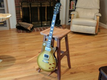 A modified version of the bench stool project with two prongs mounted to one of the bottom rails so that the stool can double as a guitar stand when not in use. The seat and guitar rests are mahogany, and the frame is sapele. (The pictured guitar belongs to my brother. I did not make it.)