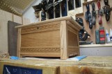 Faux-jacobian frame-and-panel blanket chest in oak sized for baby blankets as a gift for a coworker who'd just had his first child. Drawbored mortise and tenon joints, low relief carving, tongue-and-grooved cedar base, finished with Osmo wood wax and beeswax.