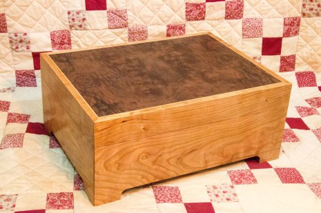 Made from Cherry with a two way bookmatched burr Walnut veneer panel on the lid, surrounded by Boxwood stringing. Finish is Danish oil