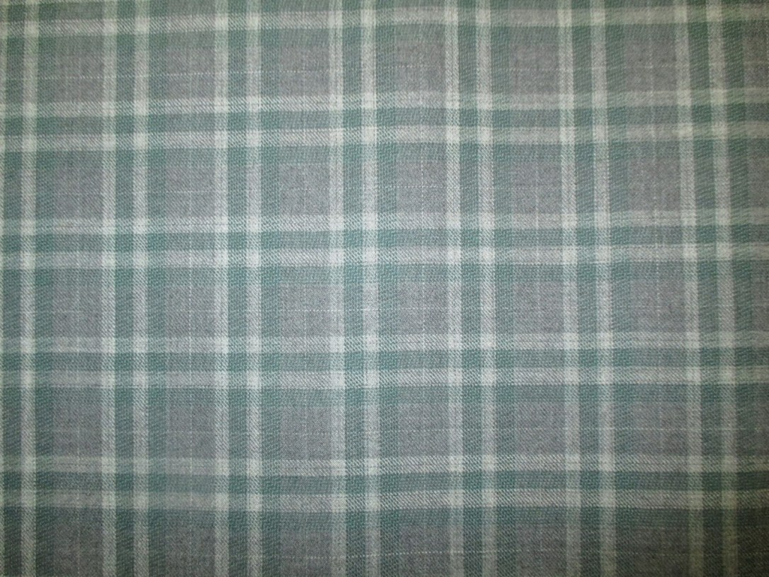 Swatch of Pendleton wool fabric in green, grey and ivory plaid.
