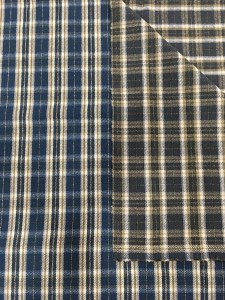 folded swatch of Pendleton wool fabric. One side is a navy, ivory plaid with thin brown lines, the other side of the fabric is brown and ivory plaid.
