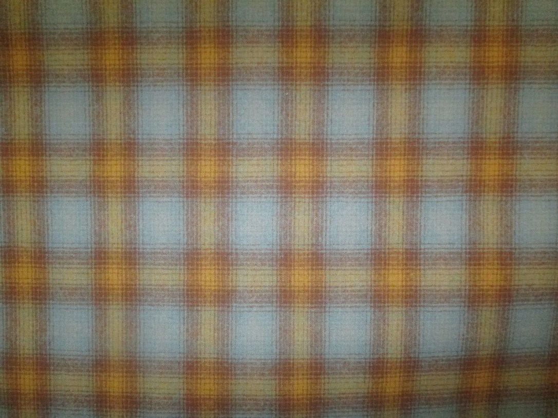Swatch of Pendleton wool fabric in ombre plaid of light blue, yellow., gold and orange.
