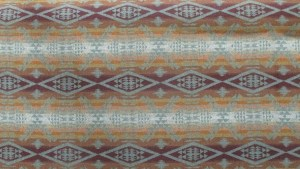 Swatch of Pendleton wool fabric in light natural tones of ivory, tan, pale orange light brown and dark brown, in a pattern of diamonds and crosses.