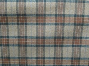 swatch of Pendleton wool fabric in plaid of rust and green on a tan mix background.