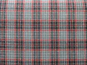 Swatch of Pendleton wool fabric with plaid of black, red, grey, accented with lines of white dobby weave.