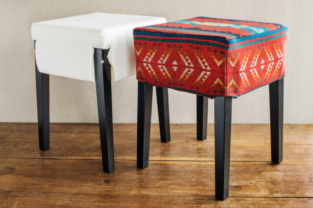 Two footstools, one covered in white fabric, one covered in red patterned Pendleton wool.