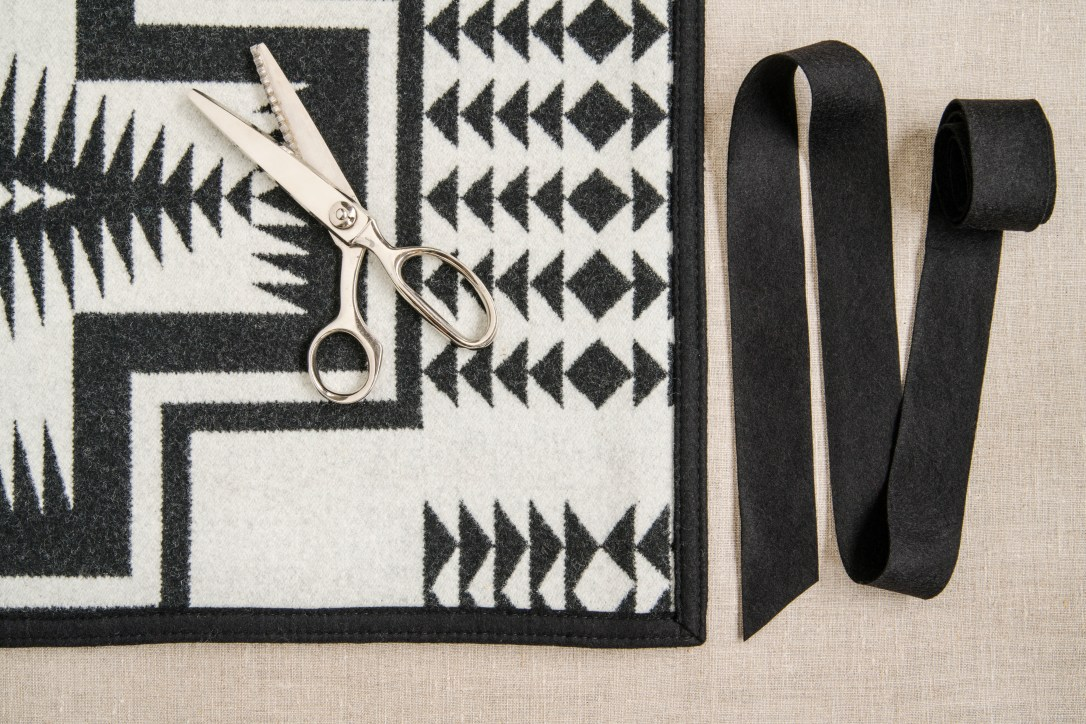 Black and white table runner made of Pendleton wool, strip of black felt binding, pair of scissors, all sitting on a grey backgound.