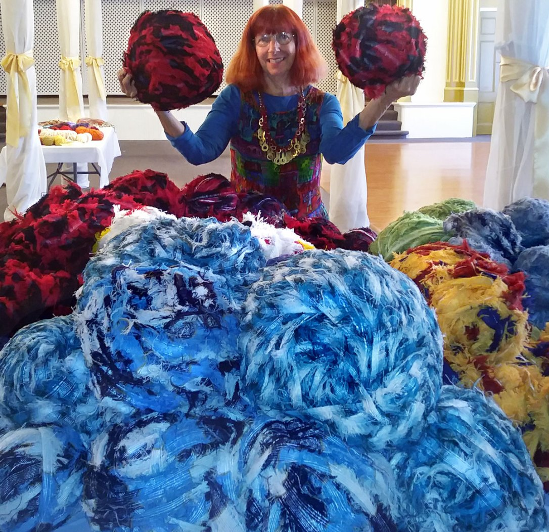 Fiber artist Bonnie meltzer poses with huge balls of Pendleton scrap wool.