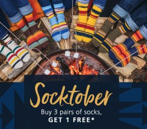 "A group of sock-wearing feet around a campfire, with the words ""Socktober Buy 3 pairs of socks, get one free"" across the bottom of the photo"