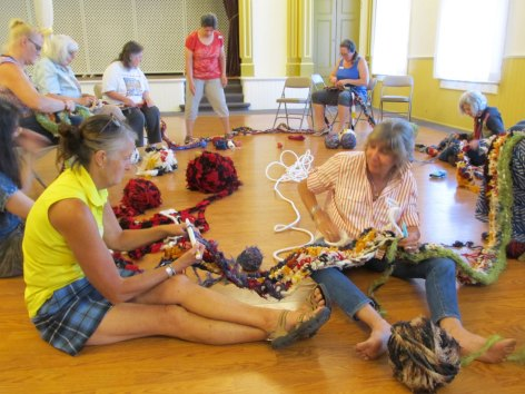 Crotcheting in a group, crafters work on a freeform crochet project led by artist Bonnie Meltzer.