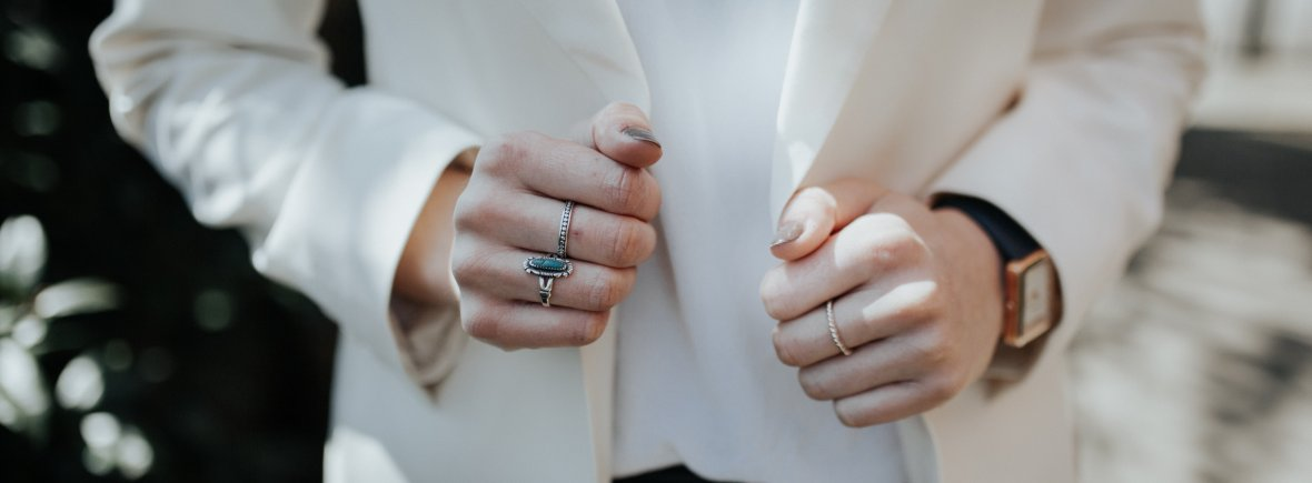 Photo shows a woman wearing a white wool blazer from the chest down. She is also wearing rings and a watch.