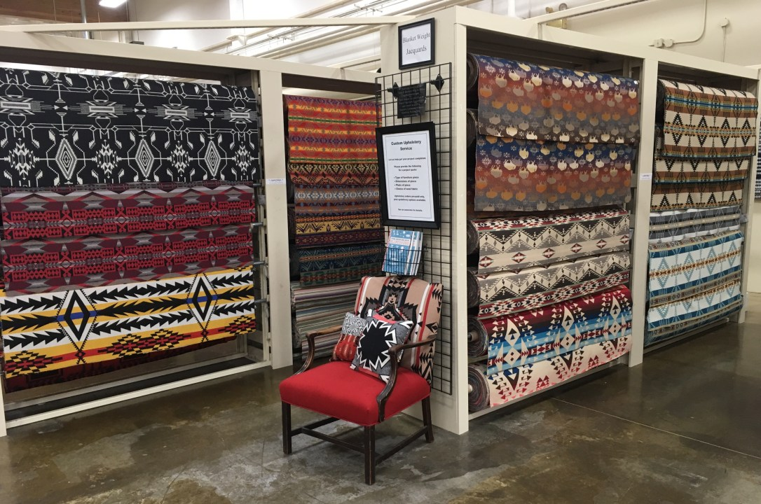 An Interior shot of the Woolen Mill Store with fabric rolls of colorful wool Pendleton fabric. A chair sits in the forground, upholstered in Pendleton wool, with Pendleton wool pillows on it.