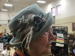Woman wearing light green wool hat decorated with feathers and yarn.