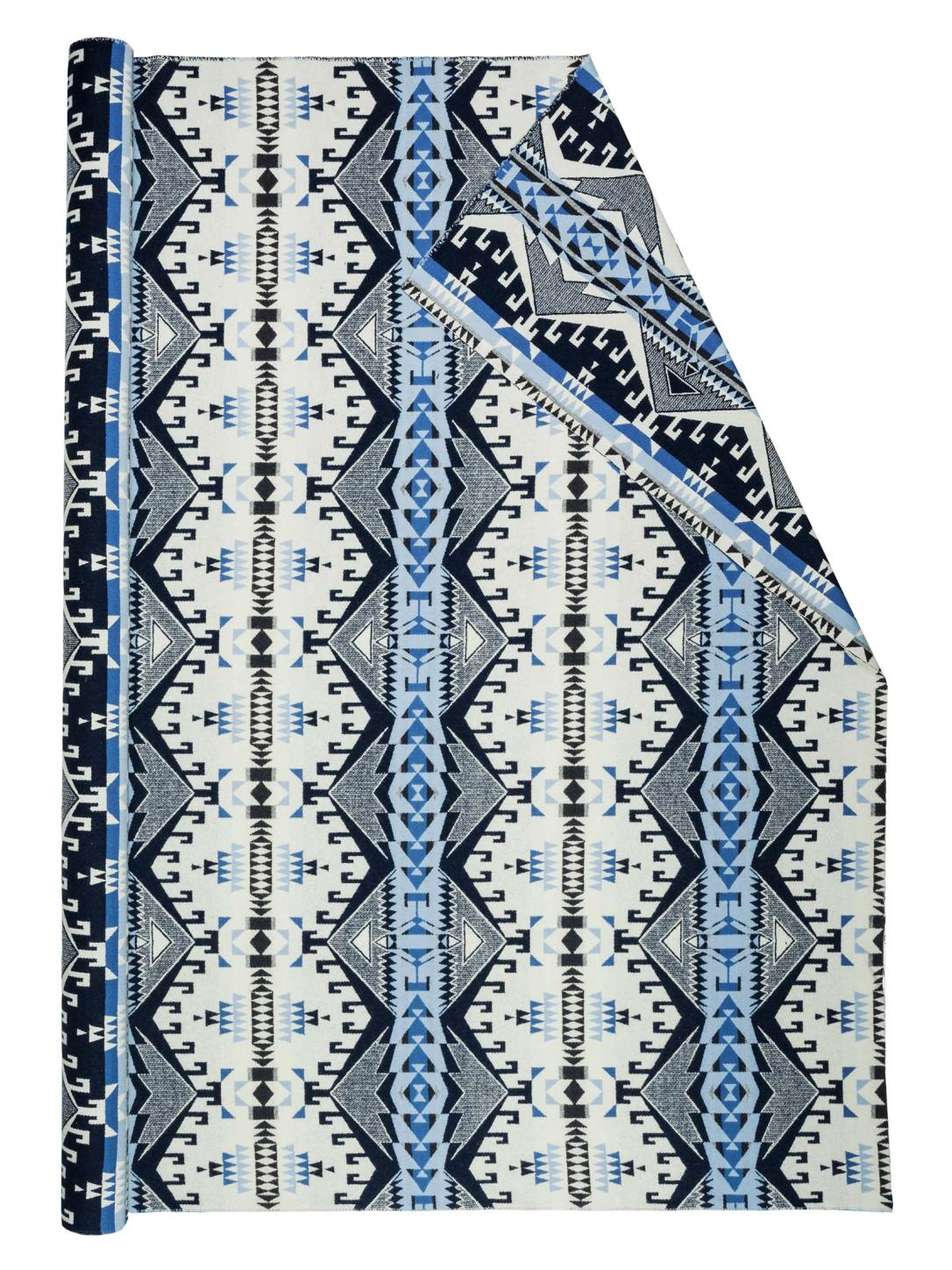 A roll of Pendleton wool fabric in Trailhead Blue, a white fabric background with a large pattern of light blue, dark blue, and black, interwoven diamond shapes with small hooks.