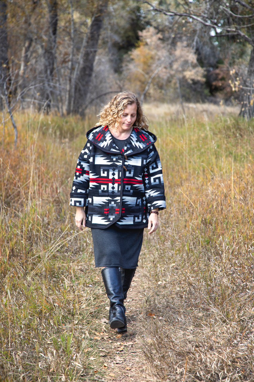 A woman with blond curly hair walks down a path in a forested setting wearing a coat made with Pendleton wool in Rio Rancho, a red and black pattern with white geometric shapes.