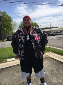 Young Native American man wears a custom letterman's jacket in Pendleton Rion Rancho wool fabric, along with red cap and basketball shorts.