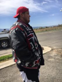Young Native American man wears a custom letterman's jacket in Pendleton Rion Rancho wool fabric, along with red cap and basketball sorts.