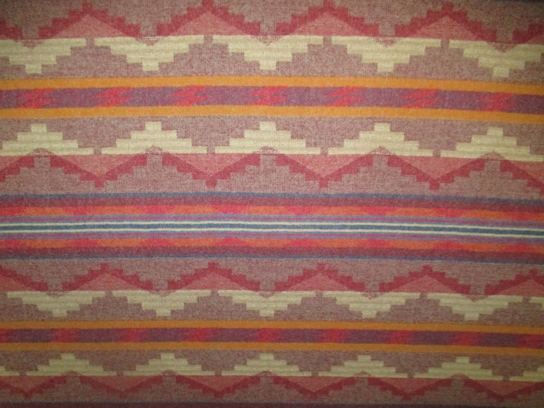 A swatch of Pendleton wool fabric in Pinetop Red. A geometric pattern in lines with steppes, in various shades of red, light brown and ivory.