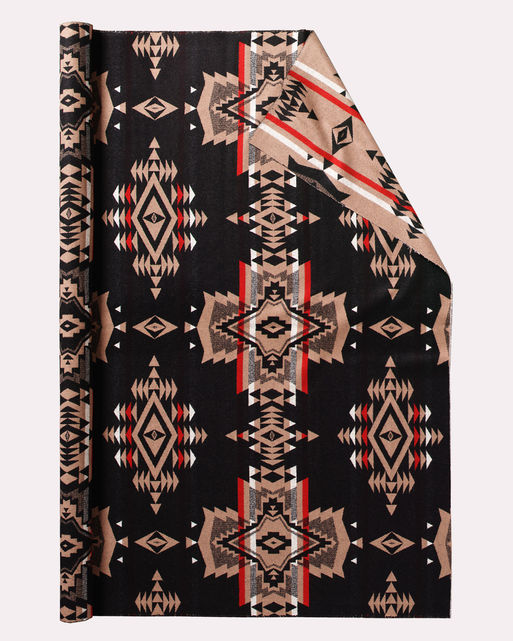 Roll of Pendleton wool fabric in Overall Black with a black background and large cross shapes in tan, white and red.