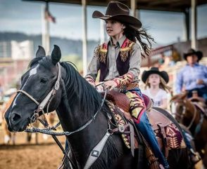 Young Western pageant princess wearing a cowboy hats and and riding outfit made with denim and Pendleton wool, riding her horse.