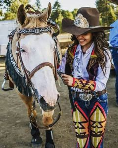 Young Western pageant princess wearing a cowboy hats and and riding outfit made with denim and Pendleton wool, with her horse.