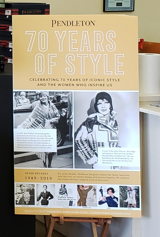 Photo of a poster with photos of Anita page, Mary Pickford, and six ads from Pendleton's past: ad for blanket coat, ad for 49er jacket, ad for wool shirt, ad for reversible skirt, ad for women's skirt suit, ad for women's sweater.