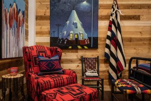 A chair upholstered in red and black Pendleton wool fabric with a matching footstool against a wooden plank wall.