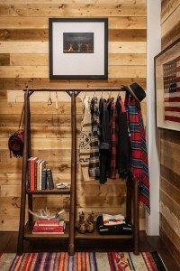 A clothing rack holding Pendleton clothes against a wooden plank wall.