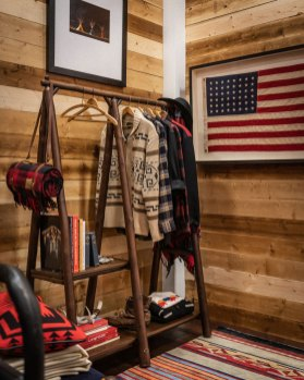 A clothes rack with Pendleton clothing hanging on it against a wooden plank wall, framed American flag hangs on wall.