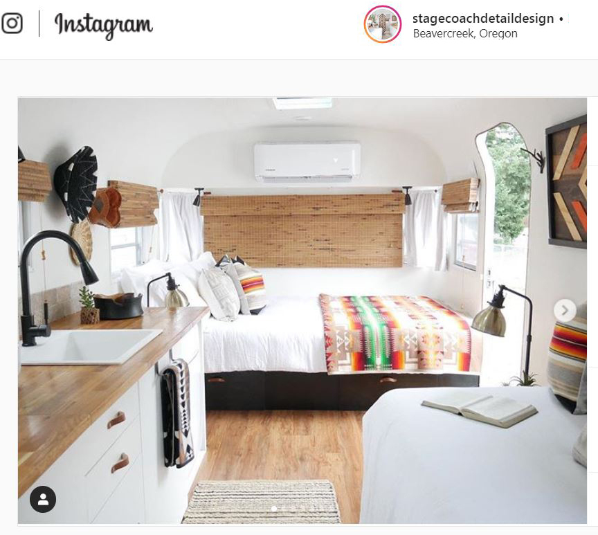 RV interior featuring a bed with Pendleton blanket and Sunbrella/Pendleton fabric pillows.