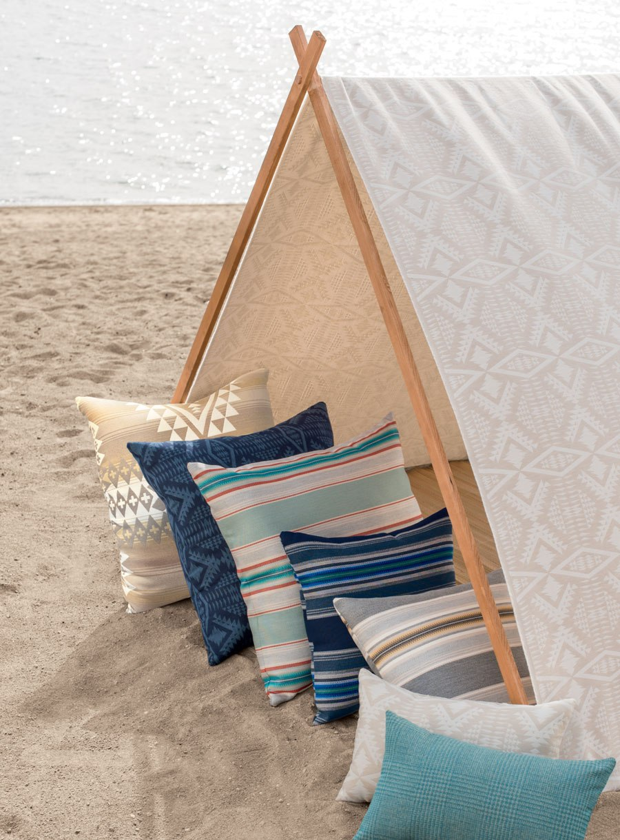 A row of Pendleton/Sunbrella fabric pillows nestled in a Sunbrella/Pendleton tent on a beach