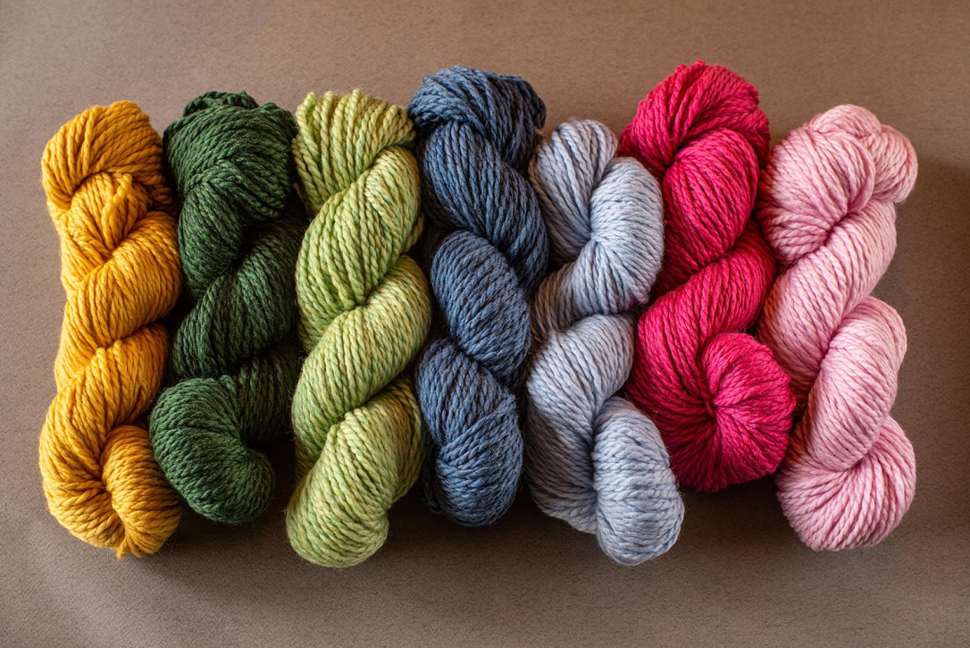 Seven skeins of Superwash 128 yarn in colors of gold, green, light green, denim blue, light blue, fucshia and pale pink.