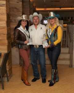 Miss Rodeo Oregon poses with Miss Rodeo Arizona and an unnamed man at the Miss Rodeo America pageant. Taylor Ann is wearing jeans, a turquoise western hat, and boots and a vest of Pendleton wool.