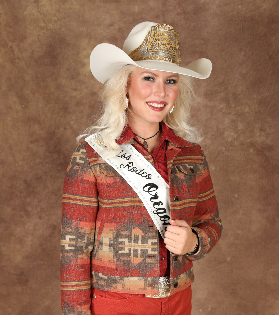 Miss Oregon Rodeo 2019, Taylor Ann Sramstad, poses for a photo wearing rust-colored jeans and a jeans-style jacket made from Pendleton wool. She is wearing herw Miss Oregon Rodeo 2019 sash, and a white western hat adorned with her title tiara.