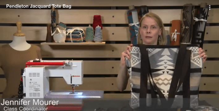 Screen shot from a free online tutorial for sewing a jacquard wool Pendleton tote bag. A blonde woman holds p the finished bag, she is seated next to a sewing machine.