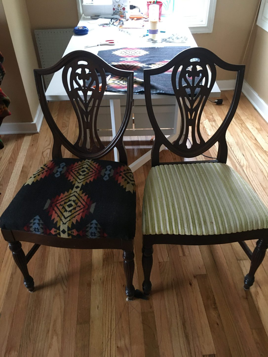 Two traditional wooden dining chairs sit side-by-side in a sewing room. The chair to the right has green striped velvet as its upholstered seat, and the chair to the left has been covered in Pendleton Pueblo Dwelling wool fabric.