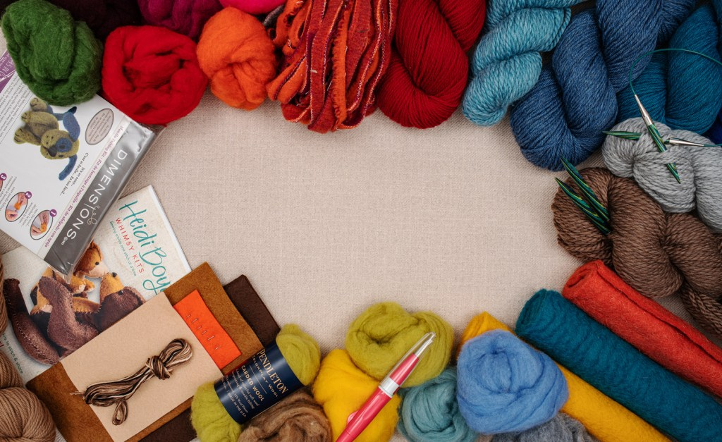 crafty photo of brightly colore yarn skeins and knitting needles arranged in a circle with pattern books