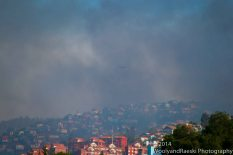 A helicopter battling the blaze disappears into the smoke from 3,000 burning homes.