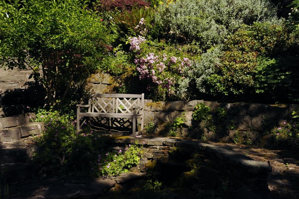 grijs bankje in de tuin
