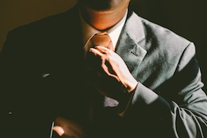 Man in a suit tightening his tie