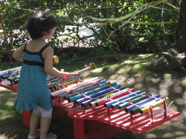 A child plays a multicolored gamelan in a park, using two mallets to strike pipes of differing lengths.